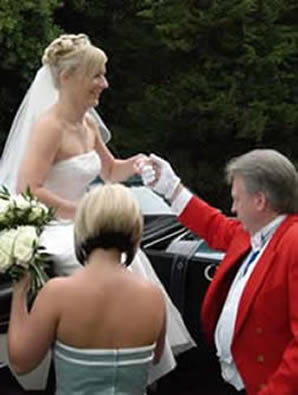 Essex toastmaster Richard Palmer assisting a bride from a horse drawn carraige